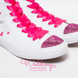 White high trainer with bright pink laces, sparkly pink toes, pink hearts on the side and personalised with date or name