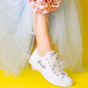 White trainer with scallapoed edge and bride on the side