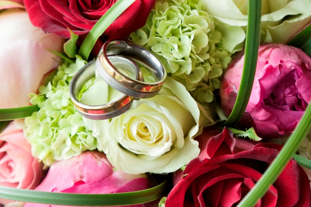 Close up of flowers and wedding bands in the centre